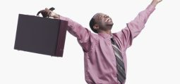 Young businessman raising hands with briefcase and mobile phone